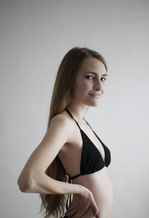 Woman in Black Bikini Standing Near White Wall