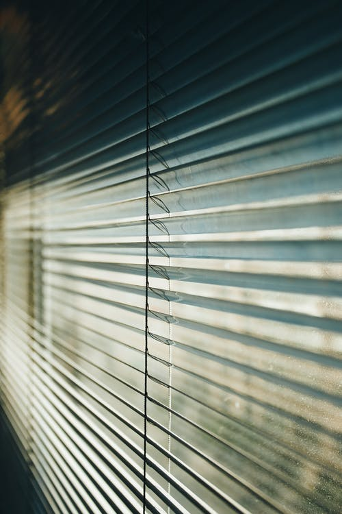 Modern metal Venetian blinds in white color covering window and sunlight coming through