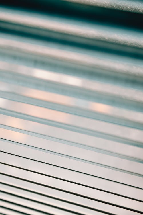 Closeup of half closed white metal blinds covering window in apartment during day