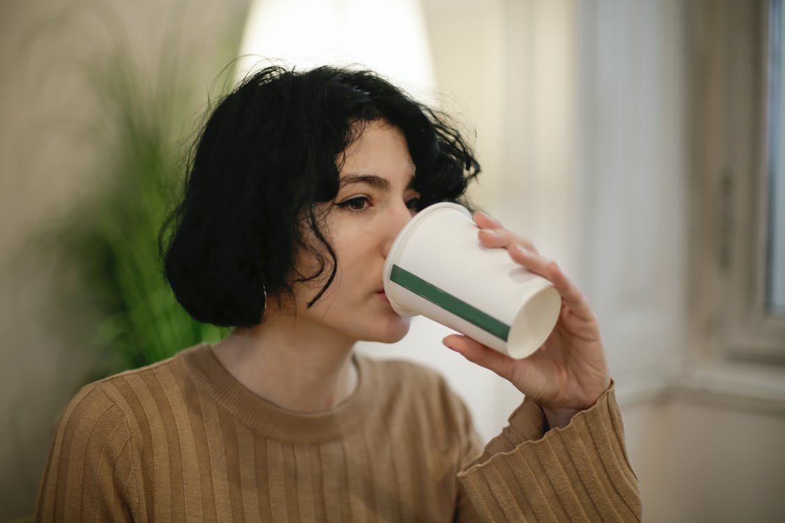 Woman in Brown Sweater Drinking on White Disposable Cup