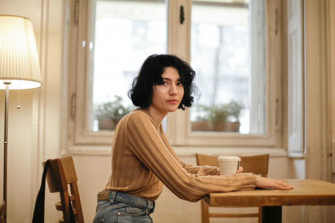 Woman Sitting on Brown Wooden Chair