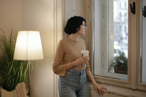 Woman in Brown Long Sleeve Shirt and Blue Denim Jeans Holding Disposable Cup