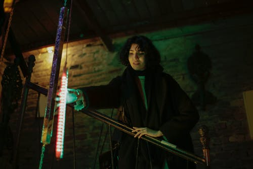 Woman in Black Coat Holding Red and White Rod Light