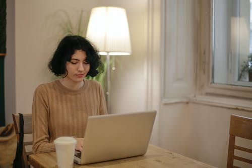 Woman in Brown Crew Neck Shirt Using Silver Macbook