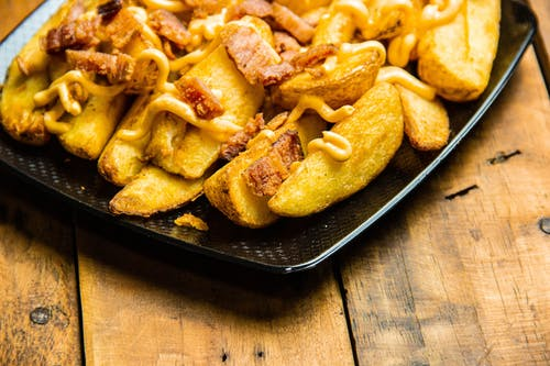Gratis stockfoto met aardappelpartjes, bacon, close-up, detailopname