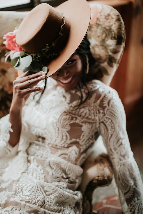 帽子をかぶって白いレースの長袖のドレスの女性