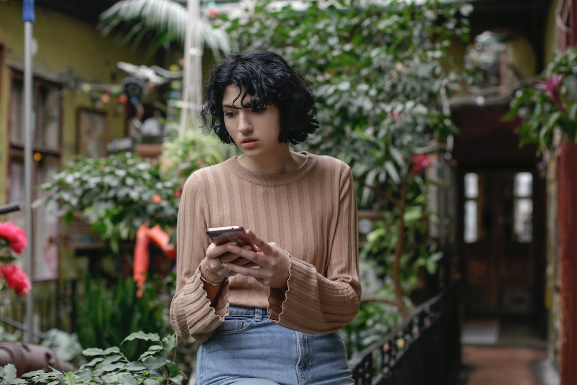 Woman in Brown Sweater Holding Smartphone