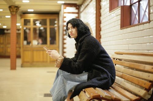 Woman in Black Sweater Sitting on Brown Wooden Bench