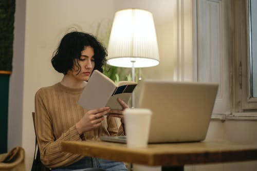 Woman in Brown Long Sleeve Shirt Holding a Book