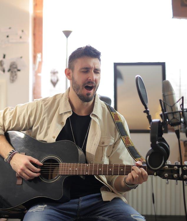 Man in Beige Button Up Shirt Playing Guitar