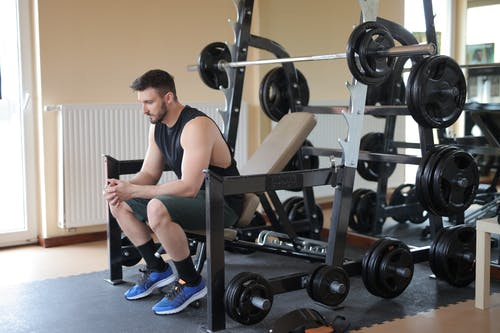 Man in Black Tank Top and Blue Nike Shoes Sitting on Bench Press