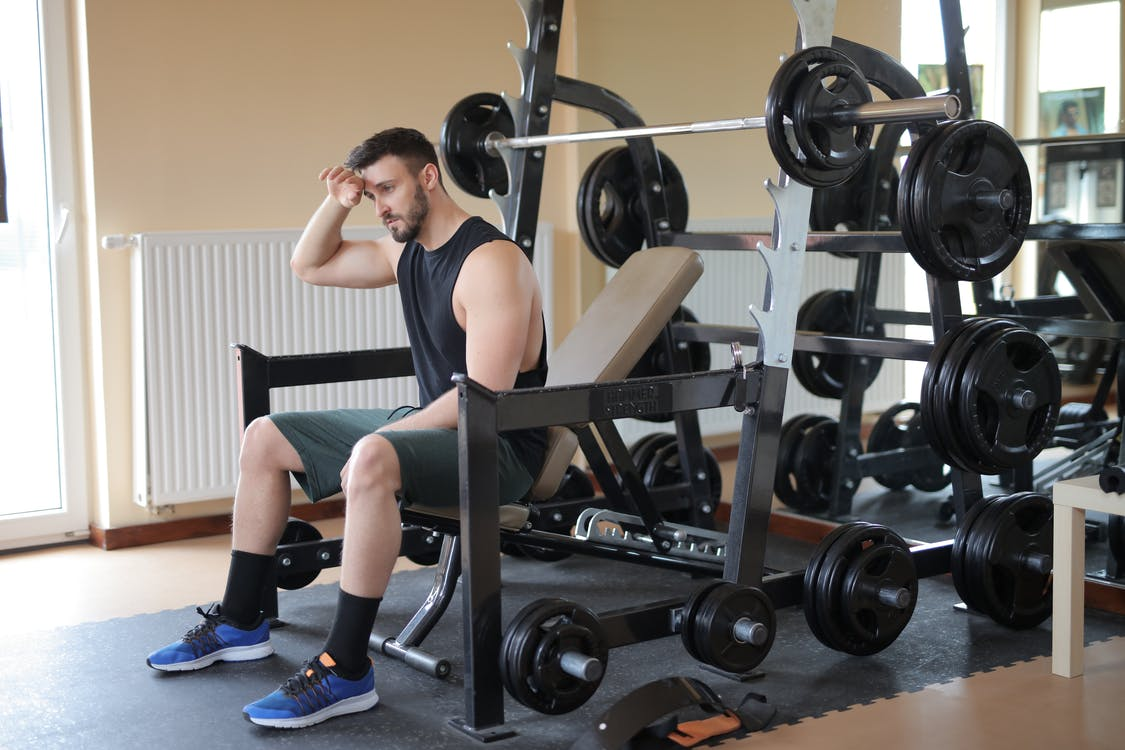 Man in Black Tank Top and Black Shorts Sitting on Black Exercise Bench