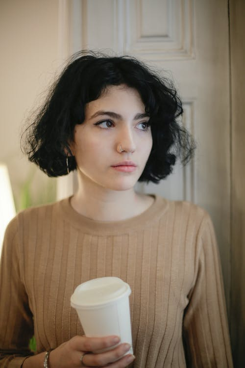 Woman in Brown Crew Neck Shirt Holding Disposable Cup