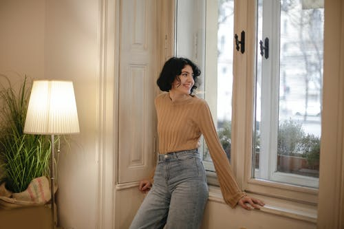 Woman in Brown Top and Blue Denim Jeans Standing Near White Wooden Window