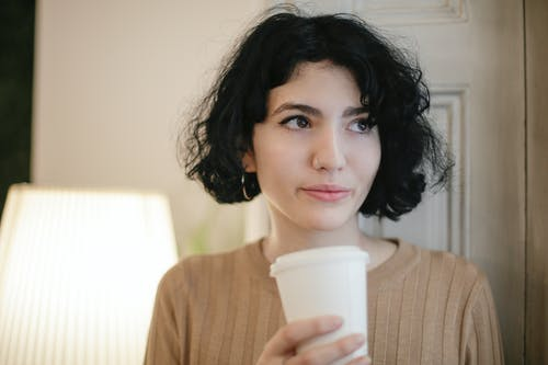Woman in Brown Sweater Holding White Disposable Cup