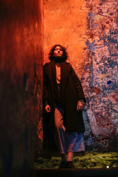 Woman in Black Coat Standing Beside Brown Wall