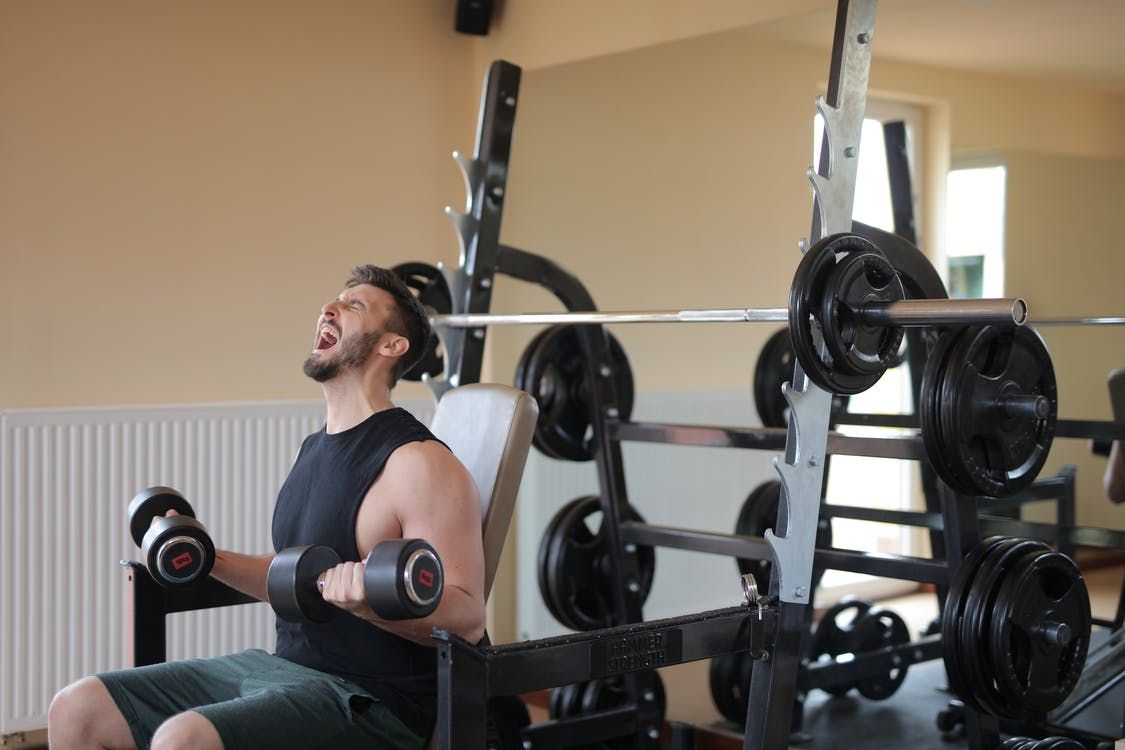 Man in Black Tank Top Sitting on Black Exercise Equipment
