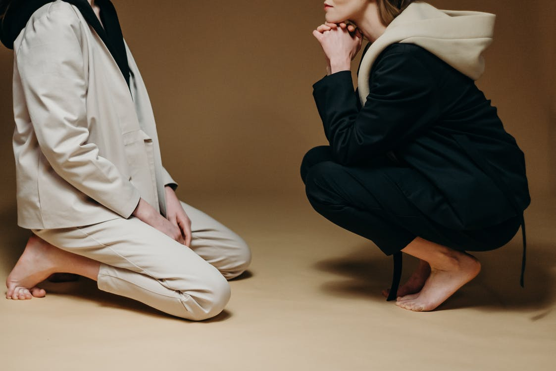 Man in Black Blazer and Beige Pants Sitting on Floor