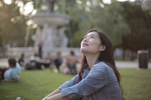 Woman in Blue Denim Jacket Sitting on Green Grass Field