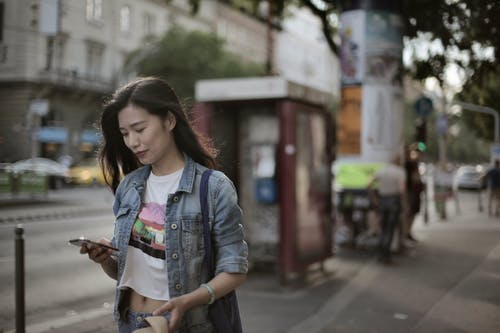 Woman in Blue Denim Jacket Walking on Sidewalk