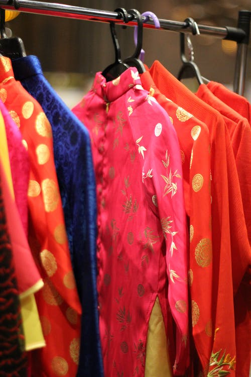 Traditional Japanese clothes of different bright colors with golden ornament hanging on cloth rack
