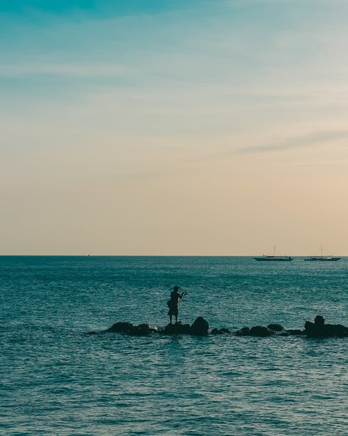 Silhouette Of Person Standing On A Rock