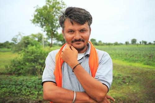 Man in White Crew Neck T-shirt With Orange Scarf