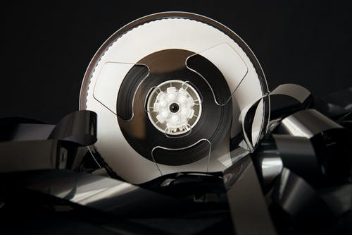 Vintage plastic bobbin with unrolled film for cinematography industry placed on black background