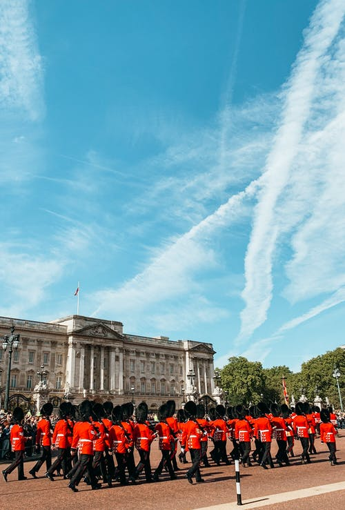 Unrecognizable Queen guards marching on square near palace against cloudy sky on sunny day in UK