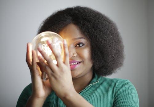 Woman in Green Shirt Holding Lightbulb