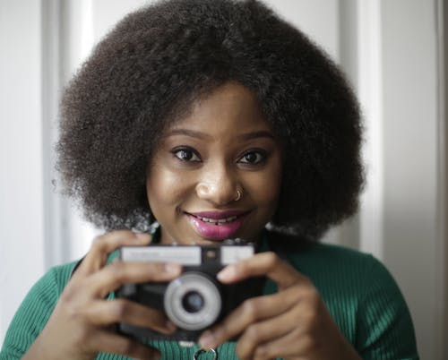 Woman in Green Shirt Holding Gray and Black Camera