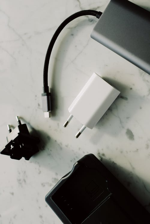 Set of various modern charging unit with adapter and small external battery pack with short cable placed on white marble table