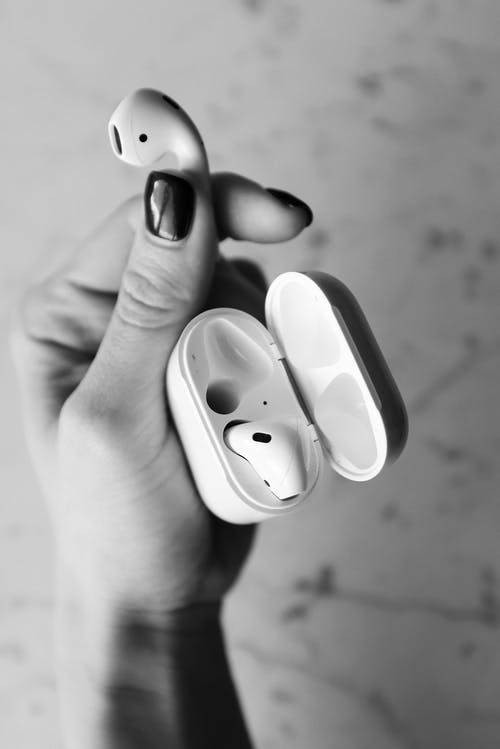 Monochrome Photo of Person Holding Apple Airpods