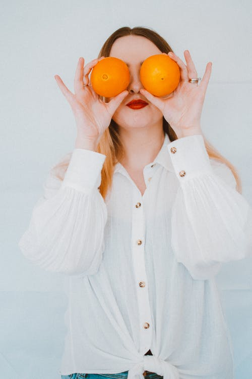 Woman iI White Button Up Long Sleeve Shirt Holding Two Orange Fruits