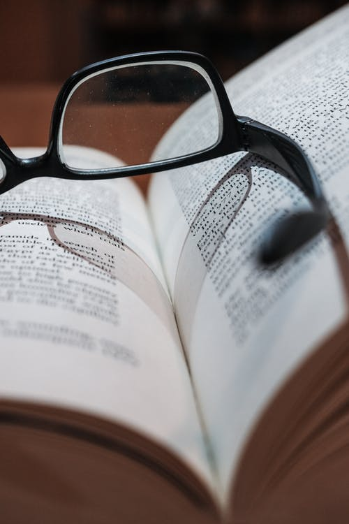 Close-Up Photo of Eyeglasses On Book