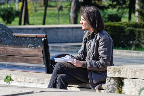 Man Writing in Notebook in Park