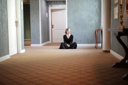 Woman Wearing Black Dress Sitting on the Floor