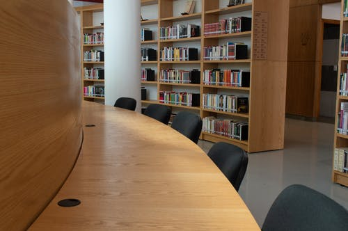 Brown Wooden Table With Black Chairs In A Library