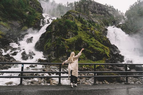 Unrecognizable female tourist enjoying view of waterfall in mountains