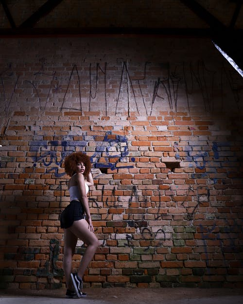 Woman Standing Near Brick Walls
