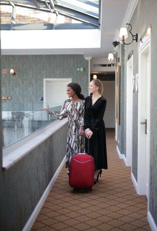 Women With A Luggage In Hotel Hallway