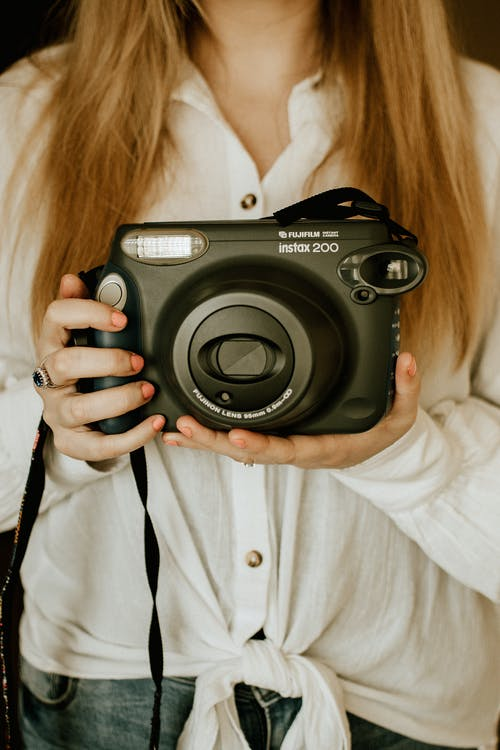 Woman Holding An Instant Camera