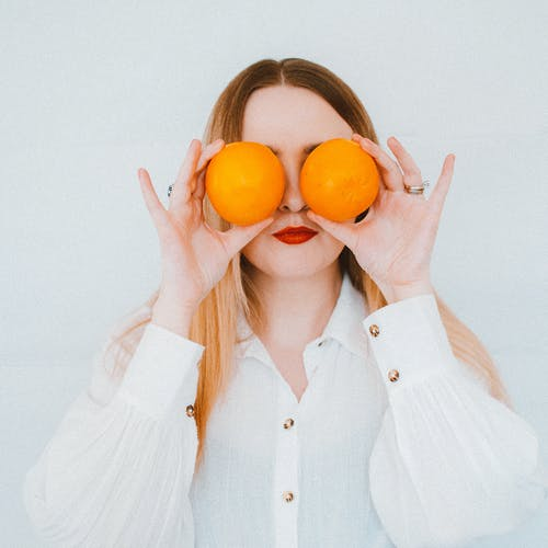 Woman In White Button Up Shirt Holding Two Oranges