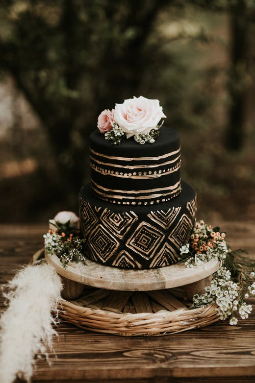 Black Round Cake With Gold Details On Brown Wooden Table