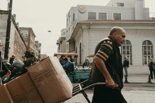 Side view of adult male pulling card with carton boxes while walking on grungy city street