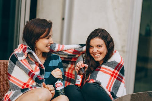 Two Women Smiling Having A Drink