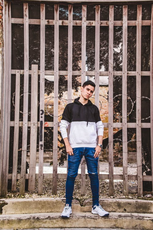 Man in White and Black Long Sleeve Shirt Standing Beside White Wooden Fence