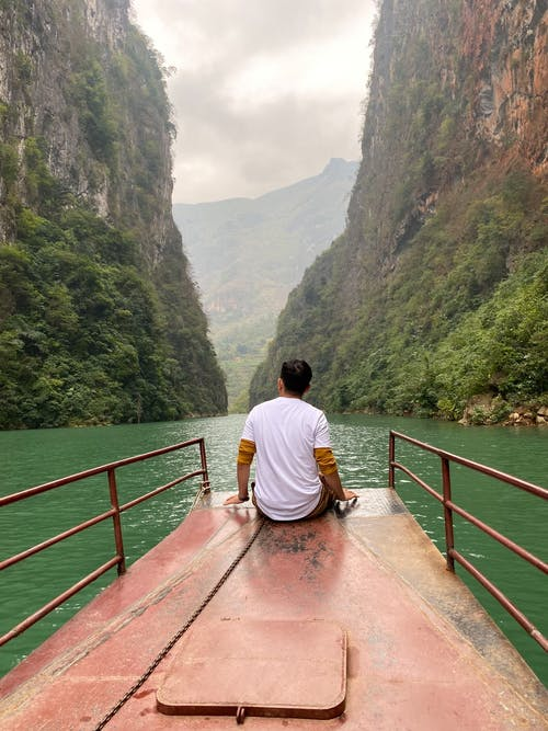 Man Sitting On Edge Of A Boat