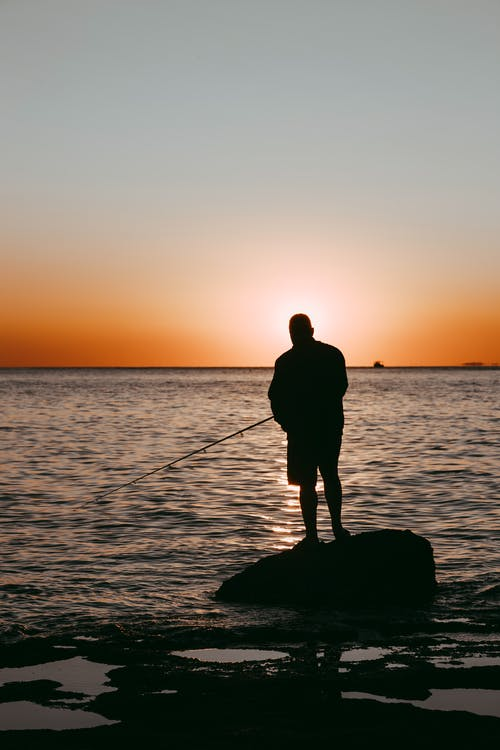 Silhouette Of Man Holding Fishing Rod Standing On A Rock During Sunset