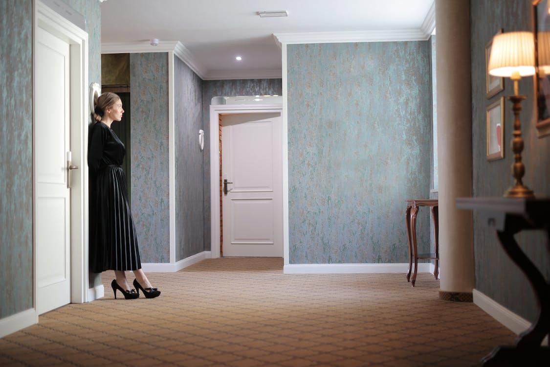 Woman In Black Dress Standing Near Door